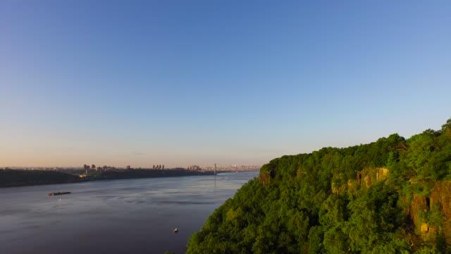 Slow motion pan over tree covered bank of Hudson River, toward George Washington Bridge