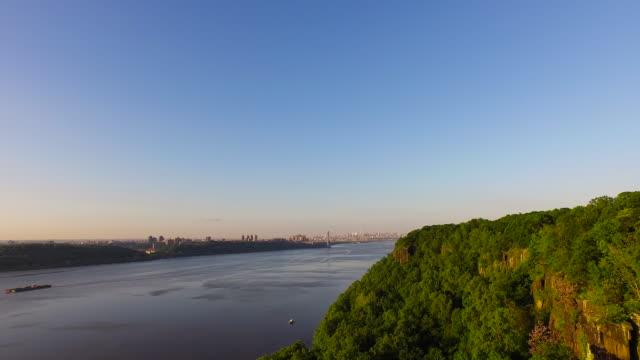 Slow motion pan over tree covered Hudson River bank, toward George Washington Bridge