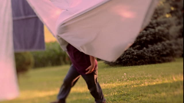 Slow motion pan young boy running through sheets on clothesline and towards camera in yard / Iowa