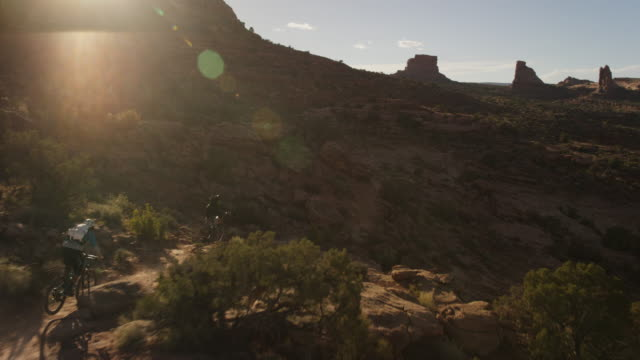 Slow motion, people ride bikes in Utah canyon