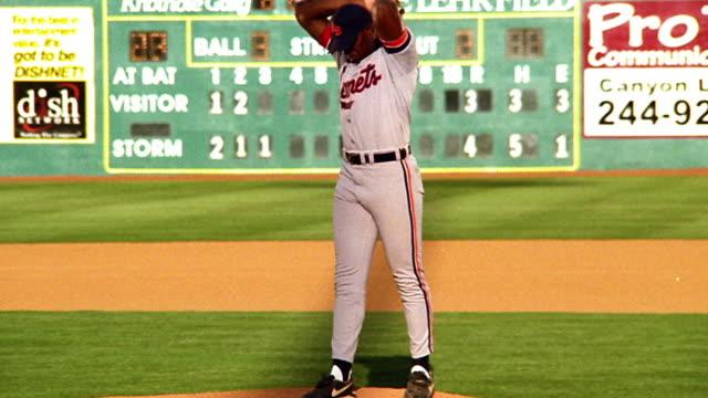 slow motion pitcher winding up with leg kick + pitching baseball / scoreboard + field in background