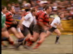 slow motion PAN of players running in rugby match