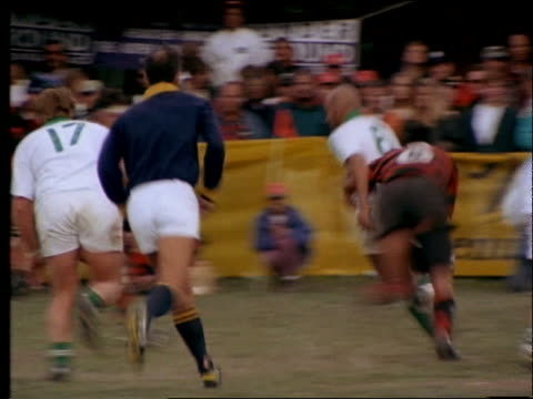 slow motion players running + tackling in rugby match