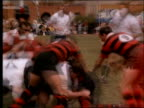 slow motion PAN of players running + tackling in rugby match