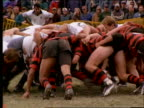 slow motion players tackling in huddle