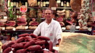 slow motion PORTRAIT man standing behind counter in deli surrounded by meats + cheeses / Florence, Italy