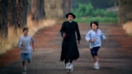 slow motion Priest + two boys running + kicking soccer ball towards camera on rural road / Italy