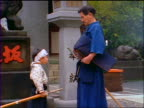 slow motion PROFILE Japanese man + small boy with kendo gear bowing to each other / Japan