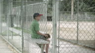 Slow motion push of boy sitting in dugout behind chain link fence.