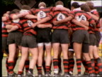 slow motion rugby players in huddle