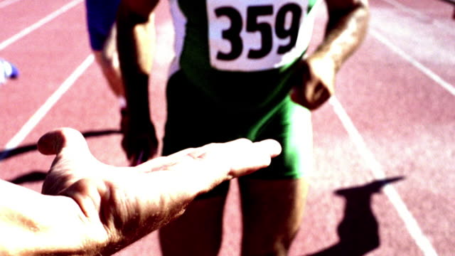 OVEREXPOSED SELECTIVE FOCUS slow motion running REAR point of view runner handing off baton to hand