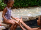 slow motion scared Black girl jumping into mother's arms in swimming pool