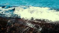 Slow motion zee golven op stenen strand