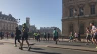 Slow motion sequence of runners at rue de Rivoli in front of Louvre during the sport event Paris Marathon 2017