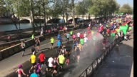 Slow motion sequence of runners rushing under a fire hose during the sport event Paris Marathon 2017