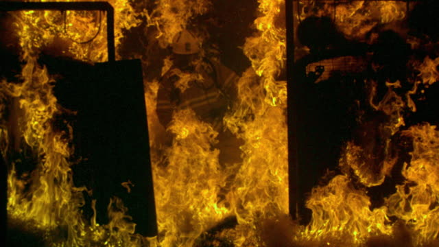 Slow motion sequence showing a fireman walking through flames during a training exercise.