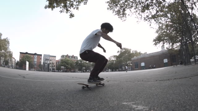 Slow Motion shot of a biracial man skateboarding through the streets of Brooklyn