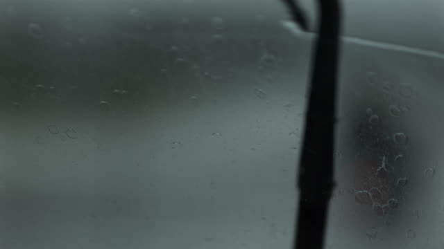 Slow motion shot of a car's windscreen wipers in motion.