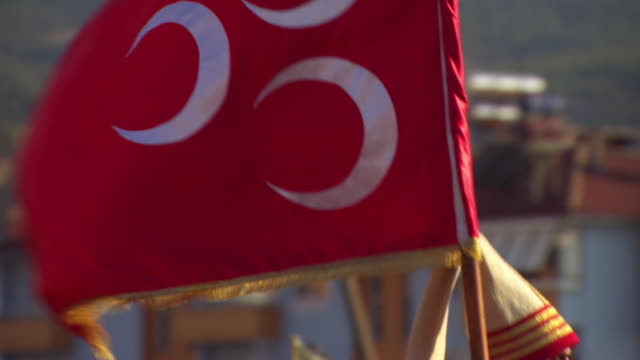 Slow motion shot of a man carrying a flag of the Ottoman Empire during a parade.