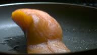 Slow motion shot of a salmon steak falling into a frying pan.