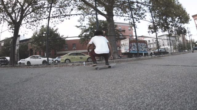 Slow Motion shot of a young man skateboarding through the streets of New York City