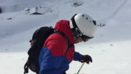 Slow Motion shot of an backcountry skier getting ready to ski down the hill through deep snow. Powder.