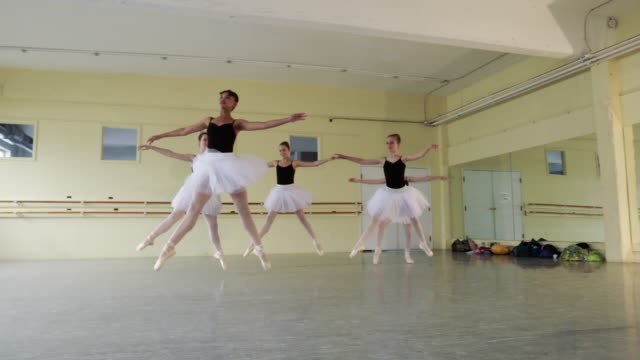 Slow motion shot of ballerinas performing split leap