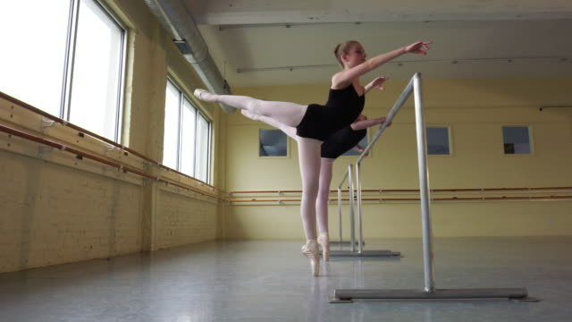 Slow motion shot of ballerinas practicing at the barre