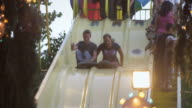 Slow motion shot of boy and girl sliging down a bumpy slide at a carnival.