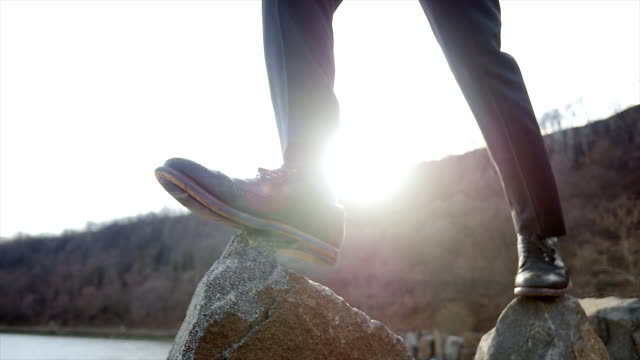 Slow Motion Shot of Carefree Man Balancing on Stones at the Shore. Nature with Trees in the Background. Symbolizing Ideas, Overcoming Obstacles, Creativity.