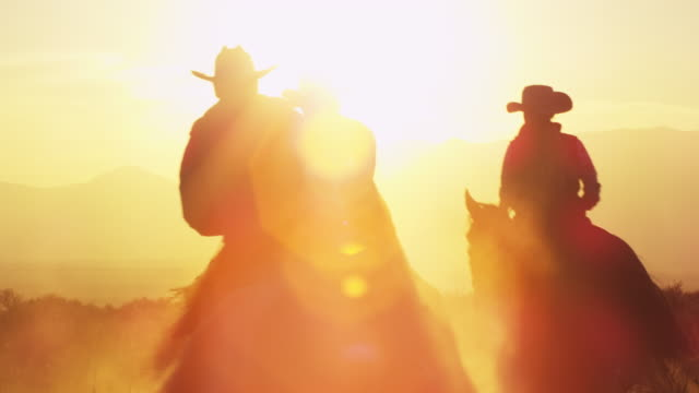 Slow motion shot of cowboys with lens flare.