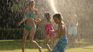 Slow motion shot of family playing in sprinkler/Sotogrande,Spain