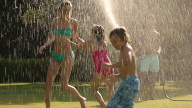Slow motion shot of family playing in sprinkler/Sotogrande,Spain