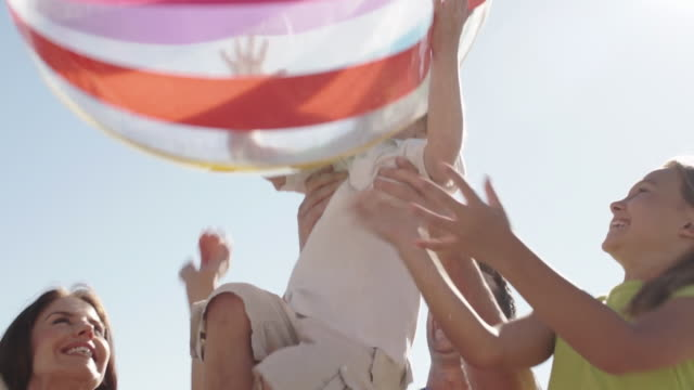 Slow motion shot of family playing with beach ball on beach.