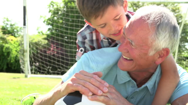 Slow Motion Shot Of Grandfather And Grandson With Football