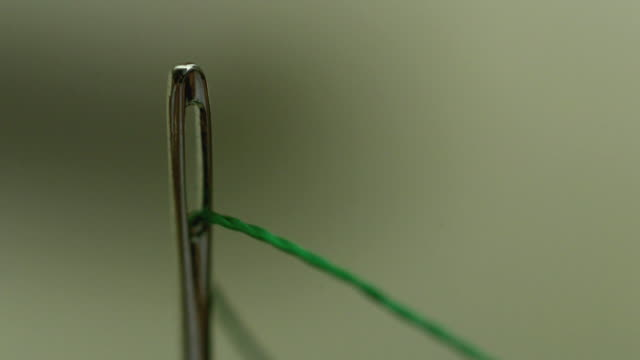 Slow motion shot of green thread being pulled through the eye of a needle.