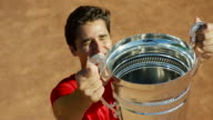 Slow motion shot of man raising tennis trophy on clay court