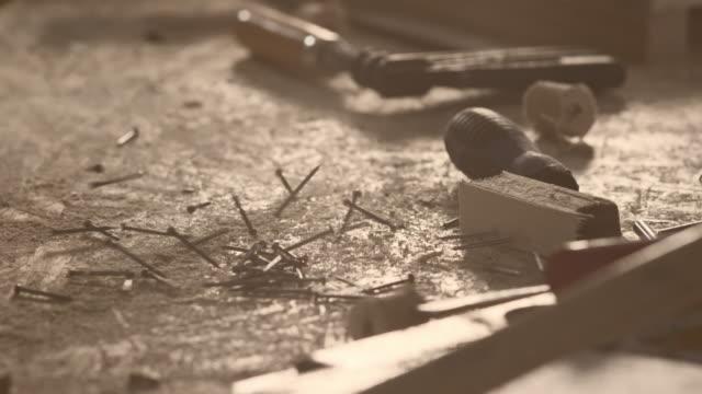 Al rallentatore girato di unghie cubi su un tavolo nel officina