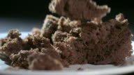 Slow motion shot of pieces of chocolate cake falling onto a plate.