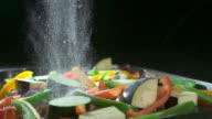 Slow motion shot of salt being sprinkled over a pan of chopped vegetables.