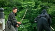 Slow motion shot of Samurai and Ninja on the bridge.