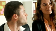 Slow motion shot of two colleagues having conversation in the office