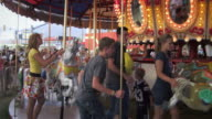 Slow motion shot of two couples getting on a merry-go-round.