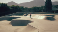 Slow motion shot of two skaters doing verious tricks at a skatepark.