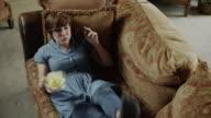 Slow motion shot of woman falling on sofa eating potato chips / Cedar Hills, Utah, United States,