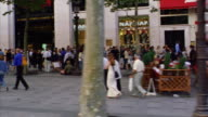 slow motion side car point of view PAN from crowded sidewalk on Champs Elysees to street with Arc de Triomphe background