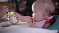Slow motion side view of baby girl being spoon fed.