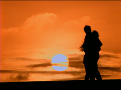 slow motion silhouette of teen couple holding hands + cuddling at sunset