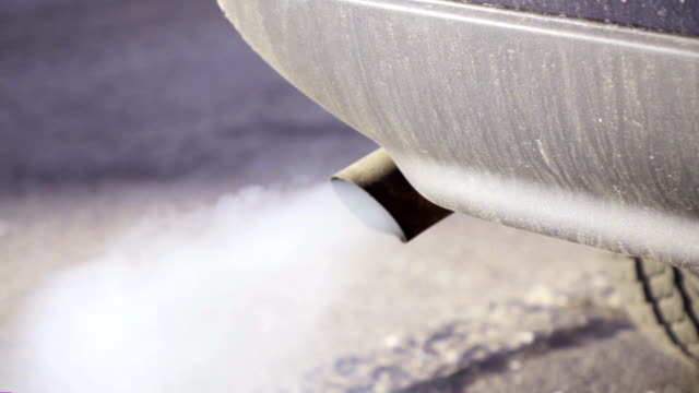 Slow motion: Smoke billows from tail pipe, pollution concept