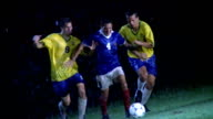 slow motion soccer player with ball chased by opposing players, losing ball + falling to ground in game